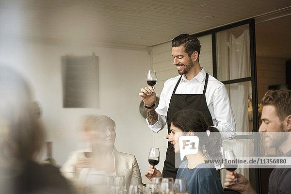 Lächelnde Menschen mit Weinglas beim Diskutieren am Tisch