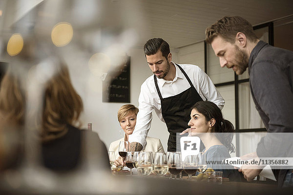 Man in apron arranging various wineglasses on table for business people