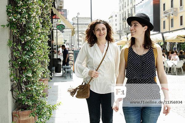 Two women strolling along city street  Milan  Italy