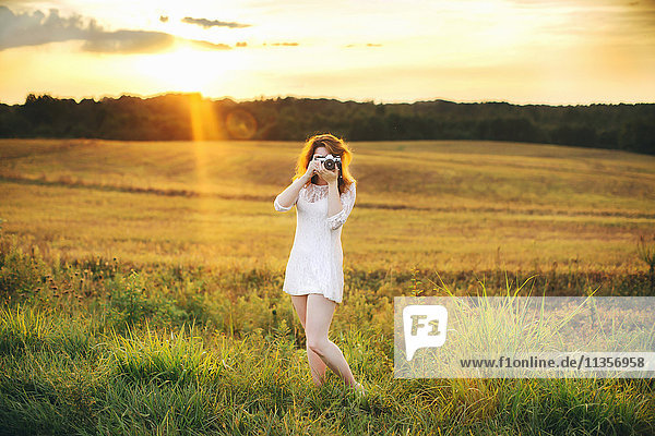 Woman in field taking photograph using camera