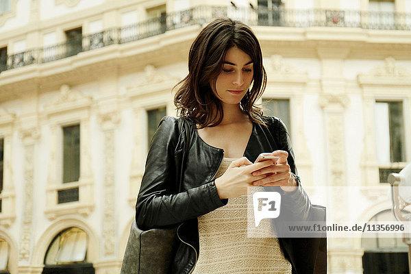 Woman reading smartphone text in Galleria Vittorio Emanuele II  Milan  Italy