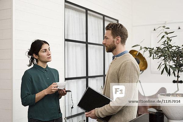 Geschäftsfrau beim Kaffeetrinken im Gespräch mit Kollegen im Büro