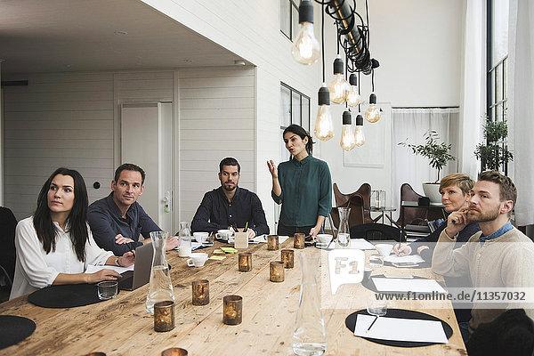 Eine Geschäftsfrau  die den Kollegen während der Besprechung am Tisch im Büro erklärt.