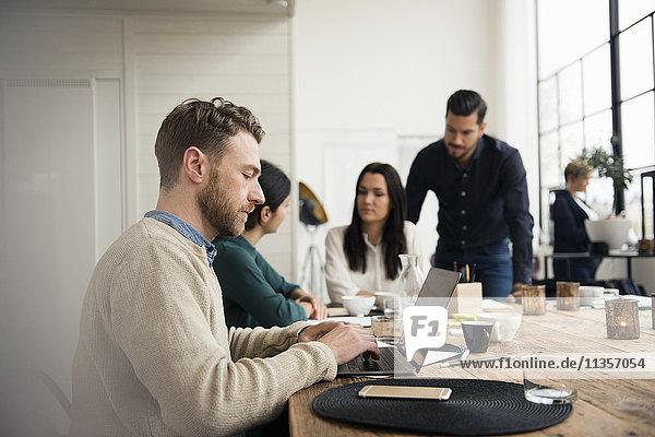 Geschäftsmann mit Laptop  während Mitarbeiter im Büro diskutieren