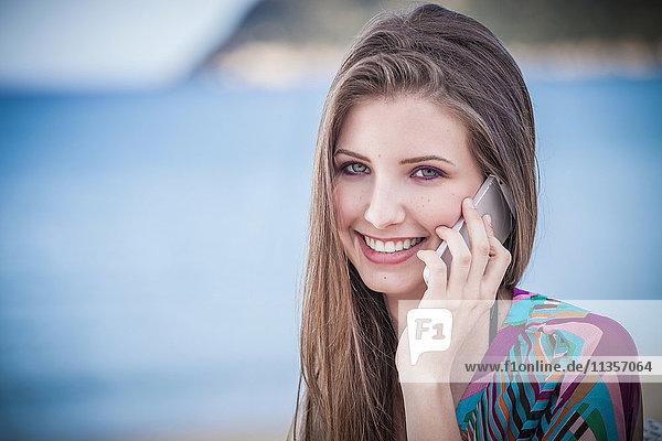 Hübsche junge Frau spricht am Strand mit einem Smartphone  Costa Rei  Sardinien  Italien