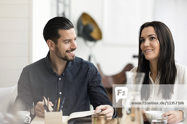 Smiling business people talking during meeting at table in office