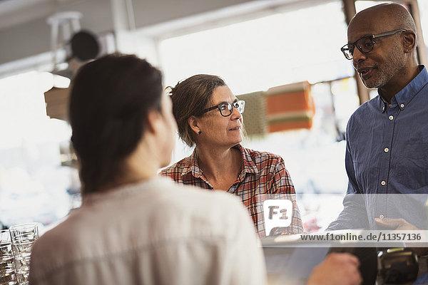 Frauen  die auf ältere männliche Kunden schauen  die sich unterhalten  während sie an der Kasse stehen.