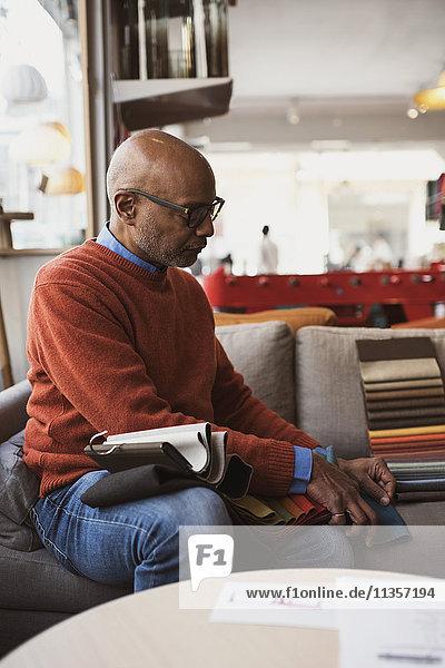 Senior Besitzer arrangiert Stoffmuster  während er auf dem Sofa im Laden sitzt.