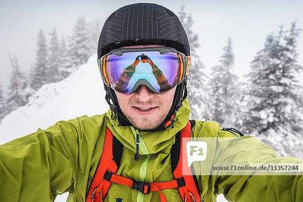 Close up of male skier wearing ski goggles taking selfie on mountain at Kranzegg  Bavaria  Germany