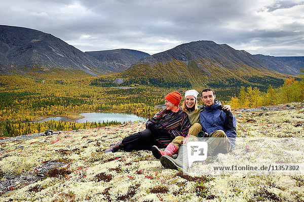 Portrait of three young adult hikers sitting together  Khibiny mountains  Kola Peninsula  Russia