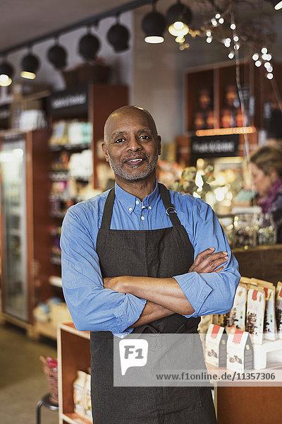 Porträt des selbstbewussten Besitzers mit gekreuzten Armen im Geschäft