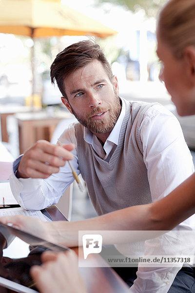 Reifer Mann und Frau sitzen vor dem Café und diskutieren