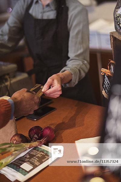 Abgeschnittenes Bild des Kunden  der die Kreditkartenzahlung an den Besitzer im Geschäft vornimmt.