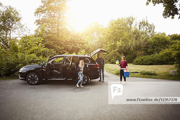 Familie mit schwarzem Elektroauto gegen Bäume im Park