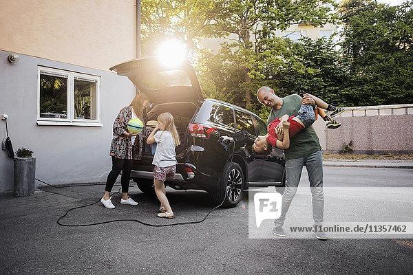 Verspielter Vater und Sohn mit Frau und Mädchen beim Auto im Hinterhof
