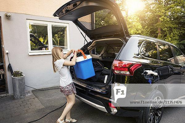 Mädchen Ladekühler in schwarzem Kofferraum gegen Haus