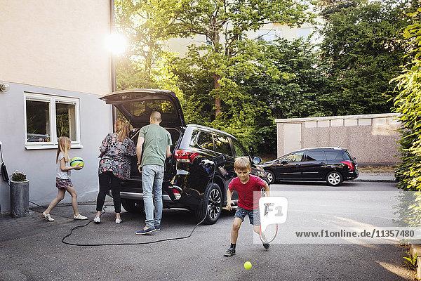 Kinder spielen mit Bällen  während die Eltern den Kofferraum im Garten beladen.