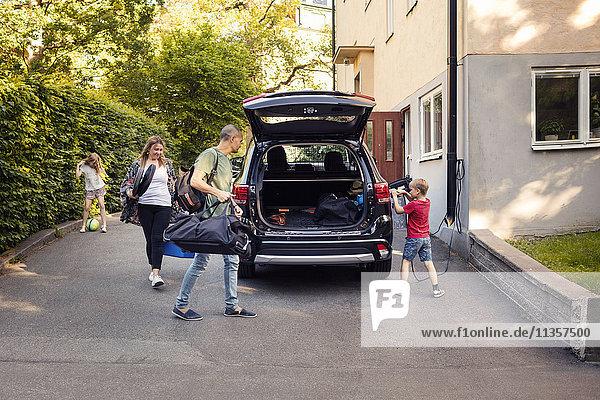 Mann und Frau laden Gepäck im Kofferraum  während der Junge das Elektroauto auflädt.