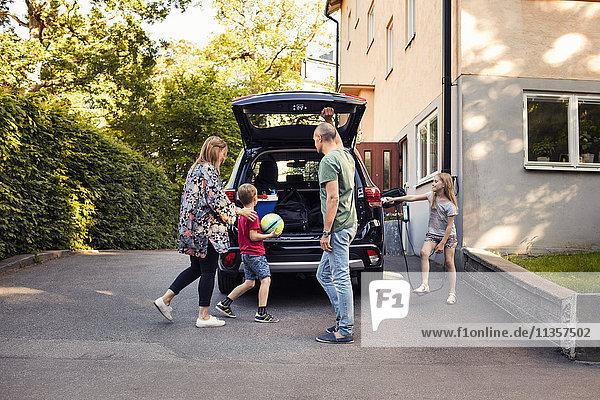 Familie steht bei Elektroauto mit offenem Kofferraum im Hinterhof
