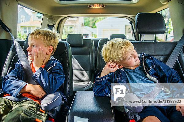 Zwillingsbrüder sitzen hinten im Fahrzeug  gelangweilte Mienen