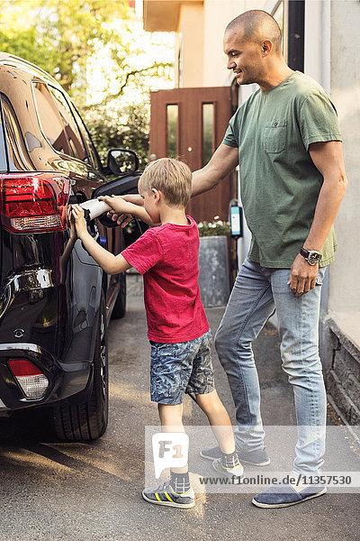 Vater und Junge laden Elektroauto nach Haus