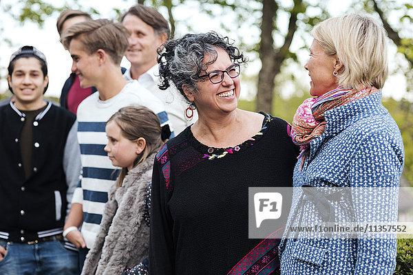 Fröhliche multiethnische Frauen  die mit Freunden und Familie im Hof stehen und sich unterhalten.