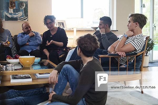 Multi-ethnische Freunde und Familie beim Reden im Wohnzimmer