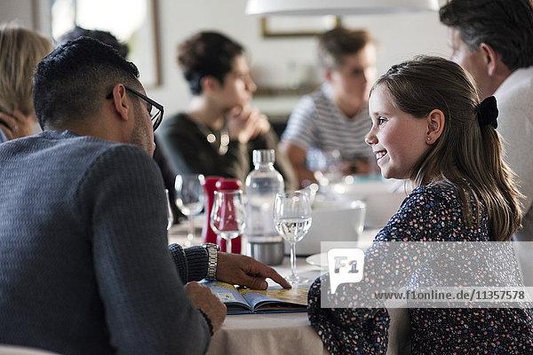 Lächelndes Mädchen  das den Mann beim Lesen des Magazins ansieht  während er mit Freunden in der Dinnerparty sitzt.