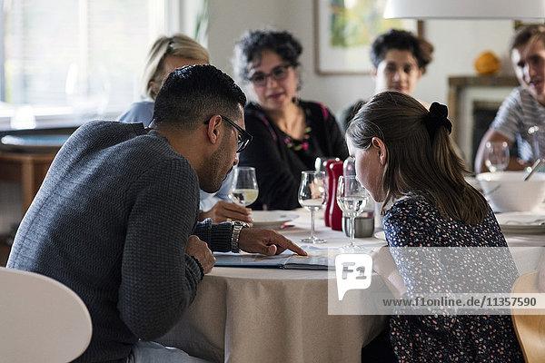 Mann liest Magazin an Mädchen  während er mit Freunden und Familie auf der Dinnerparty sitzt.