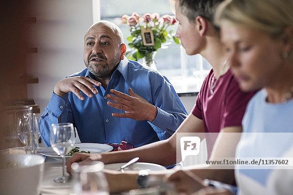 Erwachsener Mann gestikuliert  während er mit Freunden auf der Dinnerparty diskutiert.
