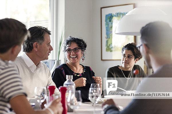 Fröhliche Freunde diskutieren am Esstisch bei der Dinnerparty