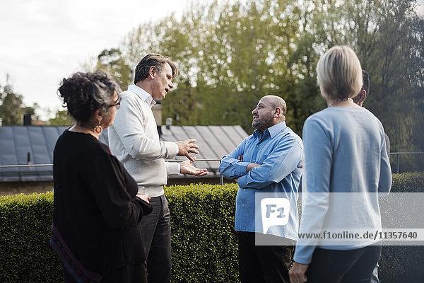 Ein reifer Mann gestikuliert  während er mit Freunden über Hecke im Hof redet.