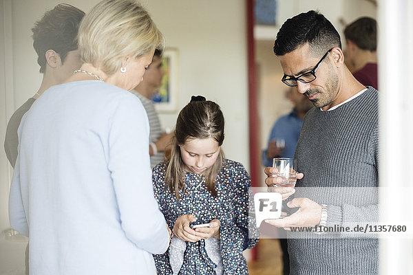 Mann und Mädchen  die telefonieren  während sie zu Hause in der Gesellschaft trinken.