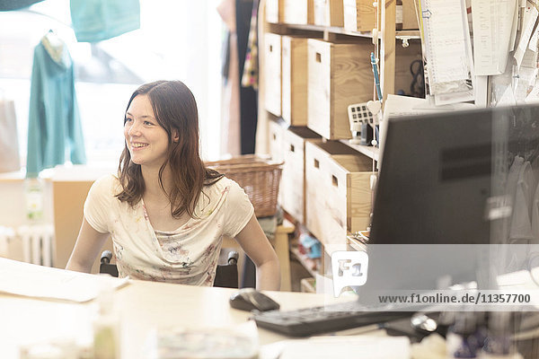 Young female shop assistant using wheelchair behind shop checkout