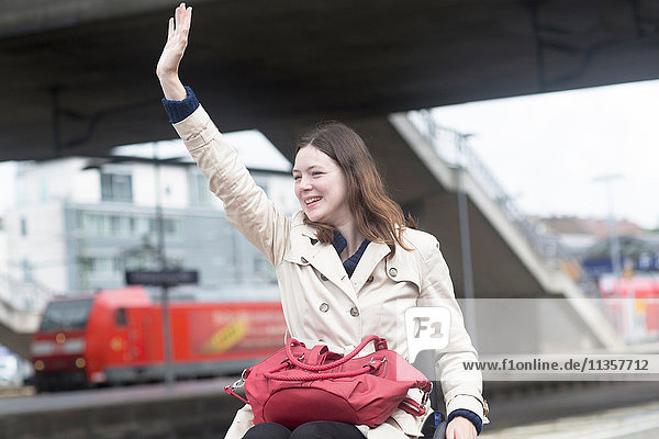 Young woman using wheelchair waving from city train station
