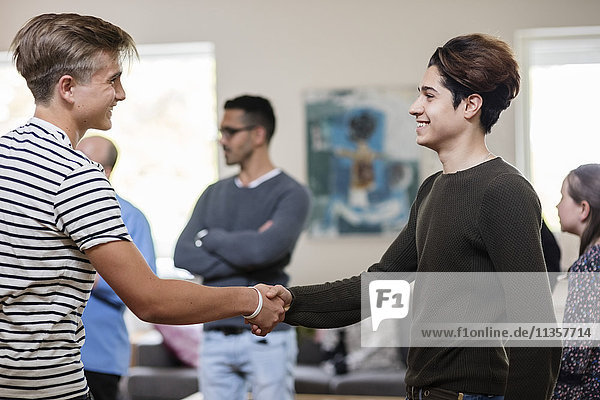 Happy multi-ethnic friends shaking hands while standing with family in living room