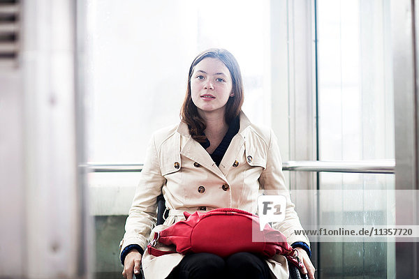 Portrait of young woman using wheelchair in elevator