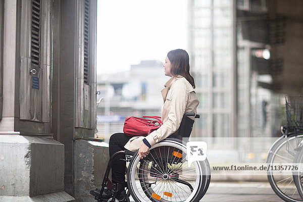 Young woman using wheelchair waiting for city elevator