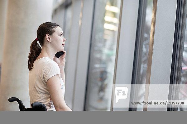 Junge Frau im Rollstuhl  die durch das Eingangsfenster blickt und über ein Smartphone spricht