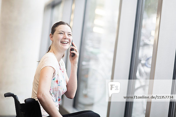 Young woman using wheelchair at entrance door talking on smartphone