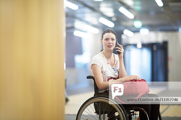 Portrait of young woman using wheelchair talking on smartphone