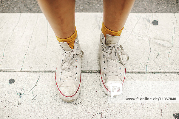 Cropped view of womans feet wearing socks and high tops