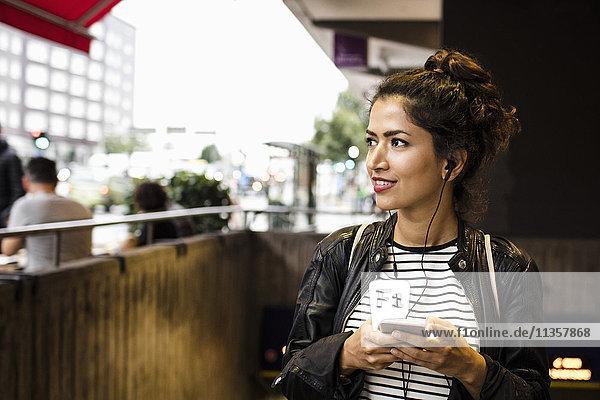 Lächelnde Frau hört Musik per Telefon in der U-Bahn-Station