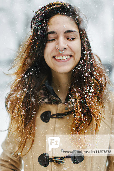 Frau mit Dufflecoat im Schnee  Augen lächelnd geschlossen