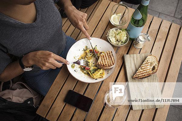 Hochwinkelansicht der Frau beim Mittagessen auf dem Bürgersteig Cafe Tisch