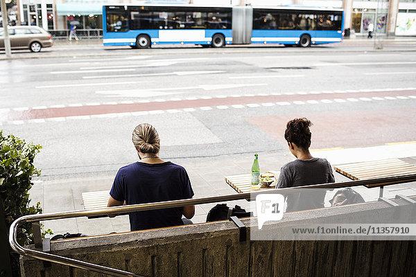 Rückansicht von Mann und Frau auf dem Bürgersteig in der Stadt