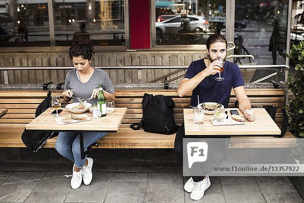 Volle Länge von Mann und Frau beim Mittagessen im Straßencafé