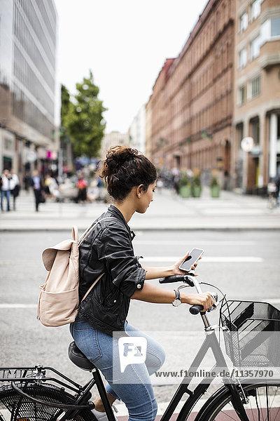 Frau schaut auf das Telefon  während sie auf der Stadtstraße Fahrrad fährt.