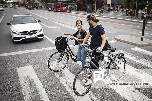 Lächelnde Freunde mit Fahrrädern über die Stadtstraße