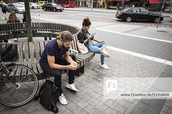 Hochwinkelansicht von Mann und Frau  die auf einer Holzbank an der Stadtstraße sitzen.